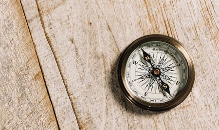 Photo pour Old compass on wood background concept for direction, travel, guidance or assistance - image libre de droit