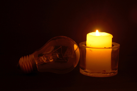 Photo for Burning candle and lamp on desktop in darkness (no electricity) - Royalty Free Image
