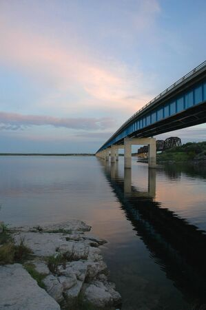 A bridge over the Amistad reservoir in western Texas is shown here from the waters edge at sunset.