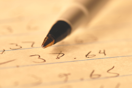 A close angle image of a ball point pen and numbers on paper.