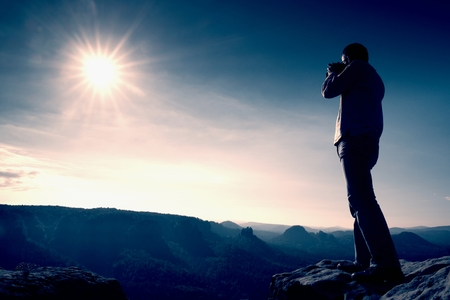Photo for Professional photographer takes photos with big camera on peak of rock. Dreamy misty landscape, hot Sun above - Royalty Free Image
