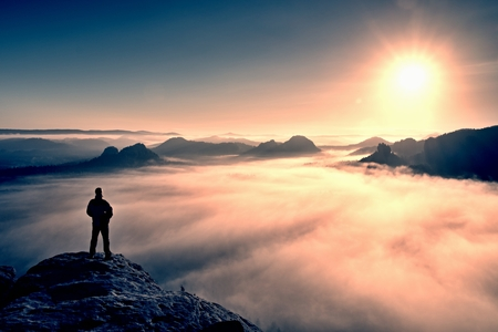 Photo pour Man stands on the peak of sandstone rock in national park Saxony Switzerland and watching to Sun. Beautiful moment the miracle of nature - image libre de droit