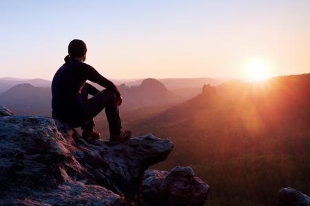 Foto de Adult tourist in black trousers, jacket and dark cap sit on cliff's edge and looking to misty hilly valley bellow - Imagen libre de derechos
