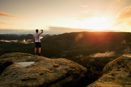 Runner on the peak. Man in his target gesture triumph with hands in the air. Crazy man in black pants and white sweaty t-shirt,