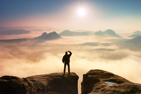 Photo pour Colorful misty morning in rocks. Tourist in dark cloths on rock empire shadowing eyes  with hand in the air. - image libre de droit