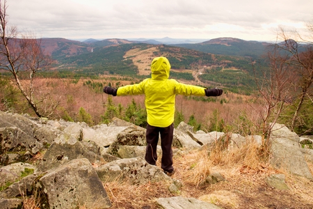 Boy in yellow warm jacket stand on a rock in a cold windy spring day. Active lifestyle, outdoor activities, hike in nature