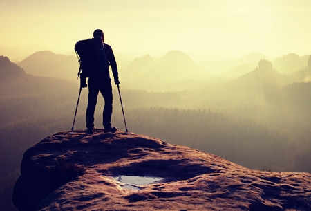 Tourist with medicine crutch above head achieved mountain peak. Hiker with broken leg in immobilizer. Deep misty valley bellow silhouette of man with hand in air. Spring daybreak