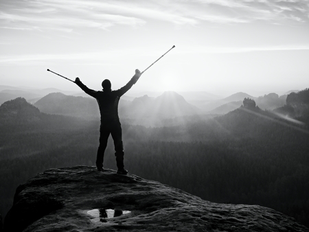 Tourist with forearm crutch above head achieved mountain peak. Hiker with broken leg in immobilizer and medicine poles hold hand in air. Colorful misty valley bellow silhouette.