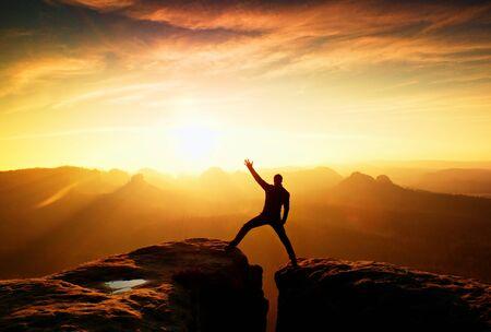 Photo pour Hiker in black celebrate triumph between two rocky peaks. Wonderful daybreak in rocky mountains, heavy orange mist in deep valley - image libre de droit