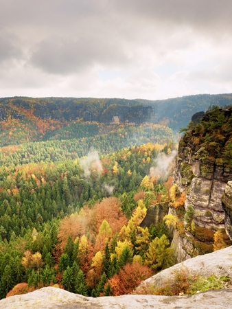 Autumnal sunrise in a beautiful mountain of Czech-Saxony Switzerland. Sandstone peaks increased from misty background, the fog is orange due to sun rays.