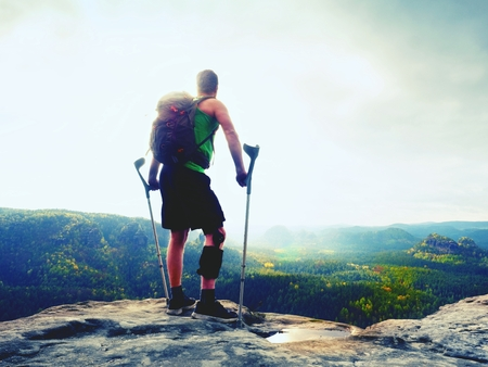 Man with a crutches and fixed broken leg on crutches. Traveler with hurt leg in bandages stay on rocky  view point in mountains.  Hiker with broken leg in immobilizer.