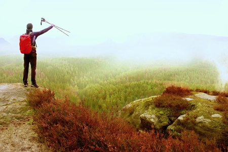 Alone adult backpacker with poles in the air,  open view on mountain valley, misty rainy day in nature. Vintage effect