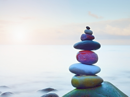 Foto de Balanced stone pyramide on shore of blue water of ocean. Blue sky in water level mirror.  Poor lighting conditions. - Imagen libre de derechos