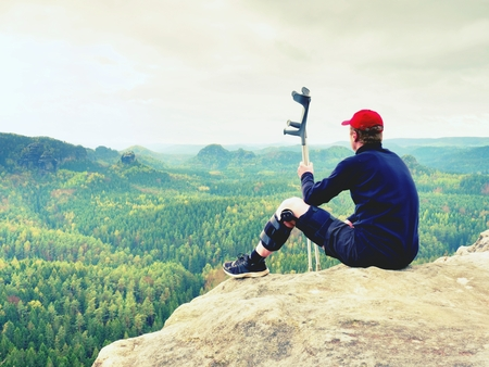Tired hurt tourist with medicine crutches. Man with  broken leg in knee brace features resting on  exposed rocky summit. Valley bellow sitting man in black sweatshirt and red baseball cap. Sharp sandstone edge.