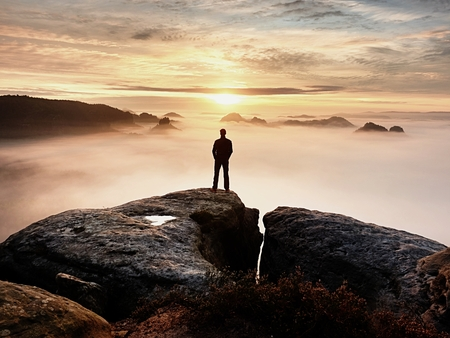Photo for Man silhouette stay on sharp rock peak. Satisfy hiker enjoy view. Tall man on rocky cliff watching down to landscape. Vivid and strong effect. - Royalty Free Image