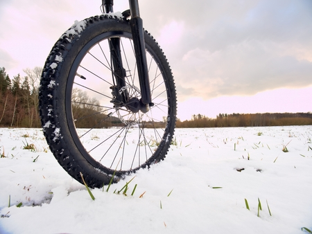 Cyclist on Mountain Bike on the Snowy Hill. Landscape  Covered with Fresh Snow. Extreme Sports and Enduro Biking Concept