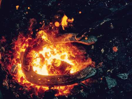 Red fire blazes inside of coal forge.  Blacksmith traditional works with hot metal  to form horse shoe from semiproduct