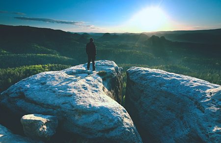 Photo for Man silhouette stay on sharp rock peak. Satisfy hiker enjoy view. Tall man on rocky cliff watching down to landscape. - Royalty Free Image