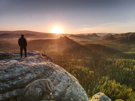 Photo pour Man on the rock empire with hands in trousers pocket  watch over the misty morning valley to rising sun at horizon. - image libre de droit
