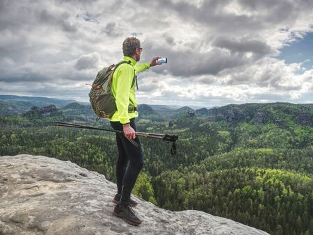 Photo for Backpacker with phone in hand. Sunny spring valley in rocky mountains. Hiker with backpack stand on rocky view point - Royalty Free Image