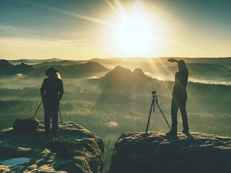 Photo pour Couple of extreme creative artists work and talk on exposed rock ledge with beautiful view into wild nature. Woman and man takes impressive photos together. - image libre de droit