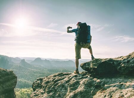 Photo pour Traveler man looking at mountain view and making landscape photo using smartphone, shinning screen - image libre de droit