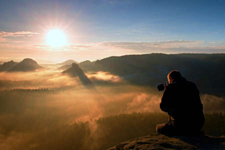 Photo pour Tourist sit on the peak of sandstone rock and watching into colorful mist and fog in morning valley. - image libre de droit