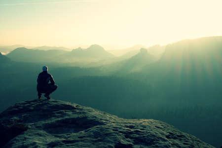 Photo pour Hiker sits on a rocky peak and enjoy the scenery - image libre de droit