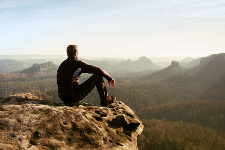 Photo pour Young man in black sportswear is sitting on cliff's edge and looking to misty valley bellow - image libre de droit