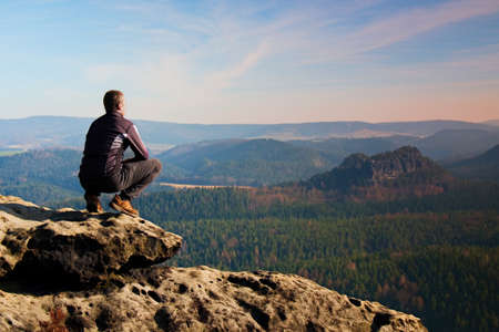 Photo for Climbing adult man at the top of rock with aerial view of the deep misty valley below - Royalty Free Image