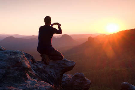 Photo for Young man in black sportswear is sitting on cliff's edge and taking photos by smart phone - Royalty Free Image