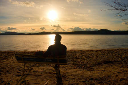 Photo for Alone Young Man In Silhouette Sitting In The Sun. Tourist take a rest on the wooden bench at autumn lake. - Royalty Free Image