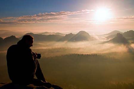 Photo pour Photographer silhouette above a clouds sea, misty mountains - image libre de droit