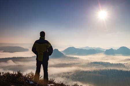 Photo for Hiking Man Silhouette enjoying amazing colorful sunset mountains. Fantastic panorama of misty and foggy layered mountains with dramatic clouds. - Royalty Free Image