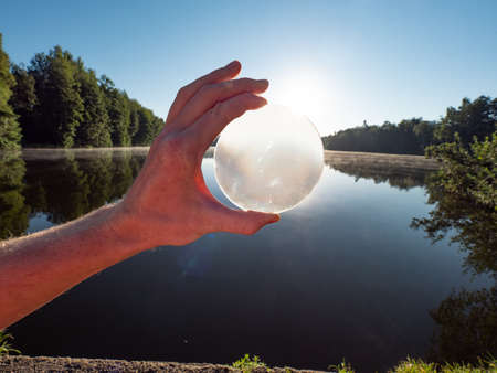 Photo pour Hand hold glass lens or ball uniquely reflects summer lake scene with sunset. - image libre de droit
