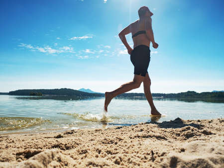 Photo for Shirtless fitness man exercising in outdoor training on the beach. Muscular man is running in water along beach, holidays concept - Royalty Free Image