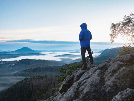 Foto für Hiking in sunrise. Man hiker wear hood and blue windcheater stay alone in sunset at mountain edge. Healthy and sport people lifestyle - Lizenzfreies Bild