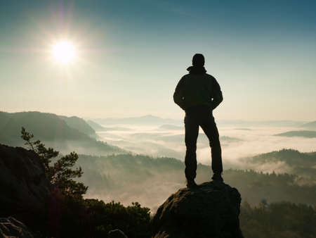 Photo for Adventure man looks at the morning horizon in the mountains during an excursion - Royalty Free Image