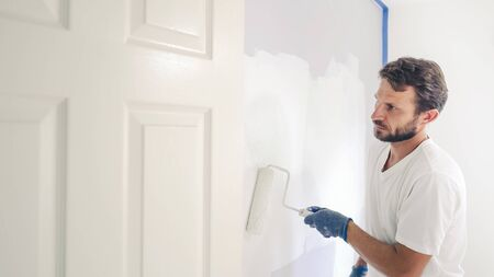 Painter man painting the wall in home, with paint roller and white color paint. Room renovations at house.