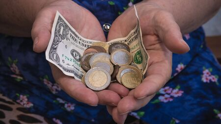 Photo for Old woman begs for alms. Closeup of money and coins in hand of poor woman. Social problems of society - Royalty Free Image