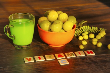 Bowl full with gooseberries, it's juice, leaves, star gooseberries and label VITAMIN C, isolated on brown background, Pune