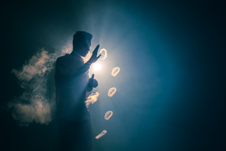 The man smoke an electric cigarette with a ring against the background of the bright light