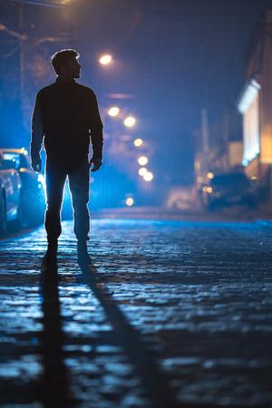 Photo pour The man stand on the rain road. Evening night time. Telephoto lens shot - image libre de droit