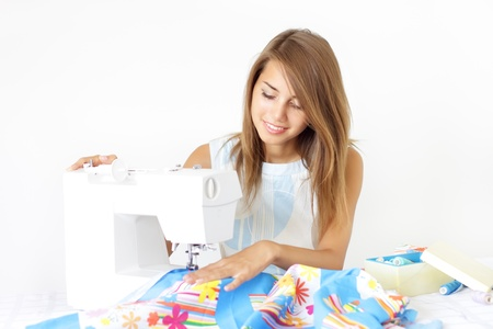 Woman using sewing machine to sew clothing