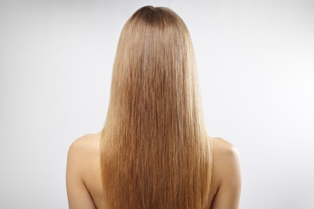 Girl with beautiful straight hair on a gray backgroundの写真素材
