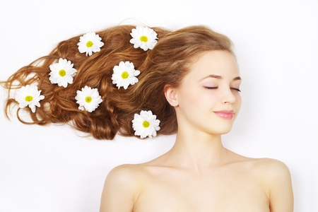 Beautiful girl with flowers in hair on a light backgroundの写真素材