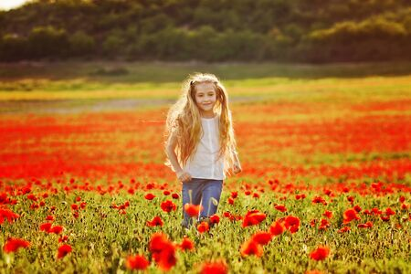 Photo pour girl running in field of red poppies - image libre de droit