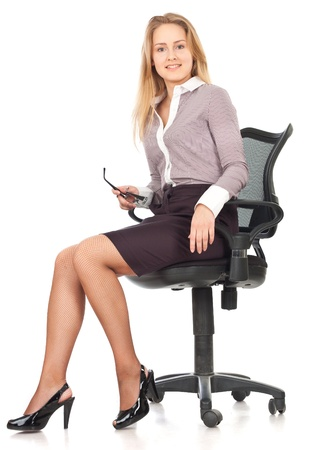 Young business secretary woman sitting in chair against white backgroundの写真素材