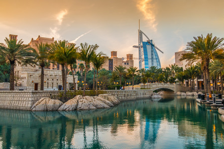 Photo pour Dubai, UAE - March 29, 2015: View on Burj Al Arab from Madinat Jumeirah during sunset. Madinat is a luxury resort which include hotels and souk spreding across over 40 hectars. - image libre de droit