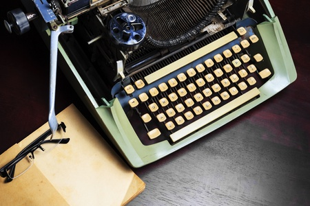 Old typewriter and old book on the table.